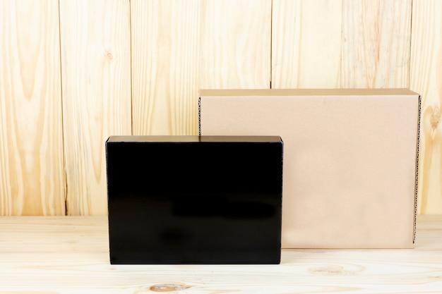 Scatola nera in bianco e scatola marrone in bianco sulla tavola di legno.