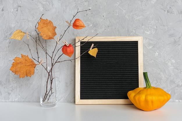 Struttura nera in bianco della bacheca e mazzo di autunno dei rami con le foglie gialle sulle mollette da bucato in vaso