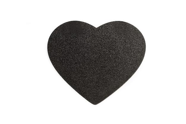 Un cuore in legno nero vuoto con spazio di copia su uno sfondo bianco