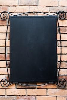 Lavagna vuota a un muro di mattoni - sfondo piacevole con spazio per il testo