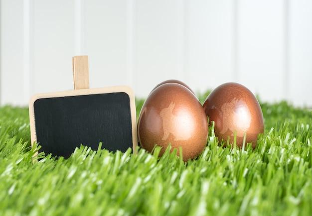 La lavagna in bianco della lavagna e le uova di pasqua di colore dell'oro di rosa del coniglio sul campo di erba verde