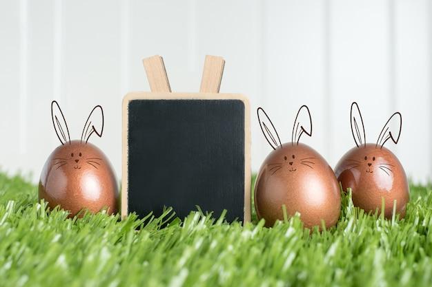 Clip di lavagna in bianco e uova di pasqua color oro rosa coniglio su erba verde
