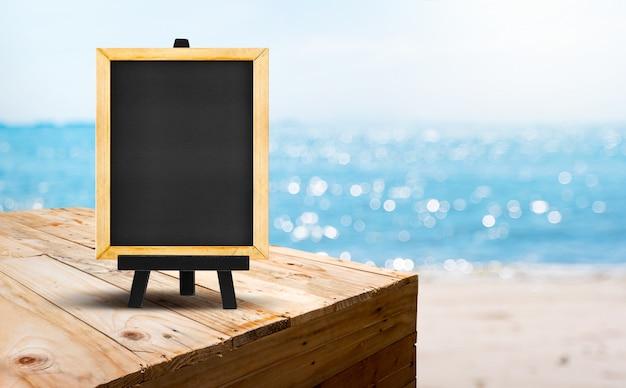 Lavagna in bianco sul supporto di legno dell'alimento della tavola con la spiaggia di sabbia della sfuocatura e mare blu con il fondo della luce del bokeh