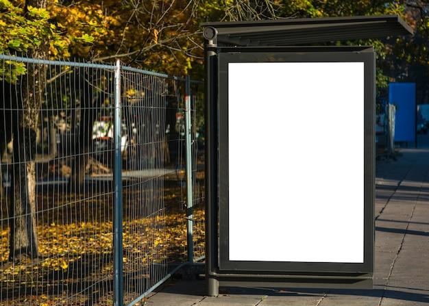 Tabellone per le affissioni pubblicitario della fermata dell'autobus in bianco nell'ambiente urbano della città.