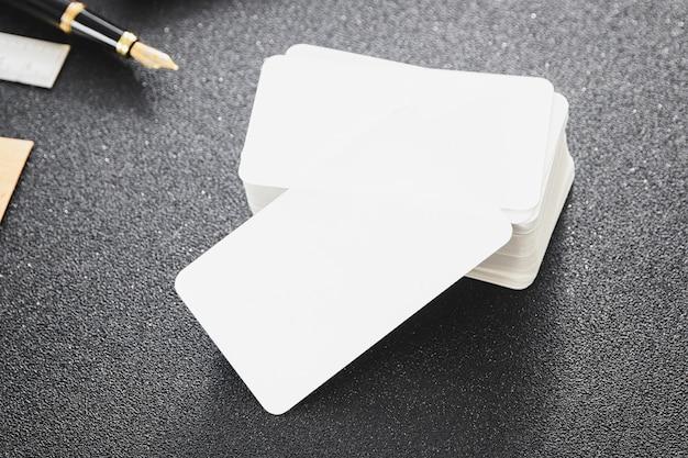 Il biglietto da visita in bianco si imbacca su una tabella scura per il contatto di affari di disegno