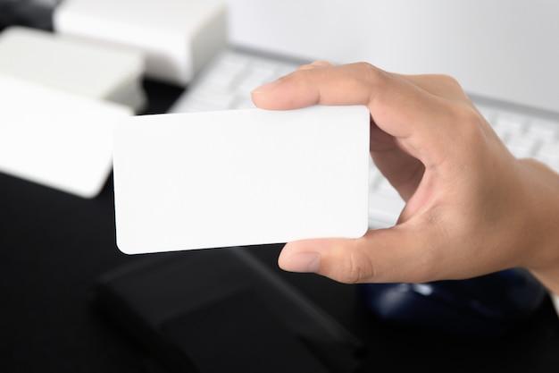 Biglietto da visita in bianco imbottigliato in mano sullo sfondo della scrivania sfocata dello scrittorio usano le informazioni di contatto templete di disegno