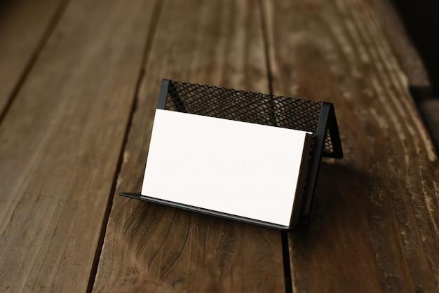 Biglietti da visita in bianco nel titolare della carta trasparente sul tavolo di legno scuro