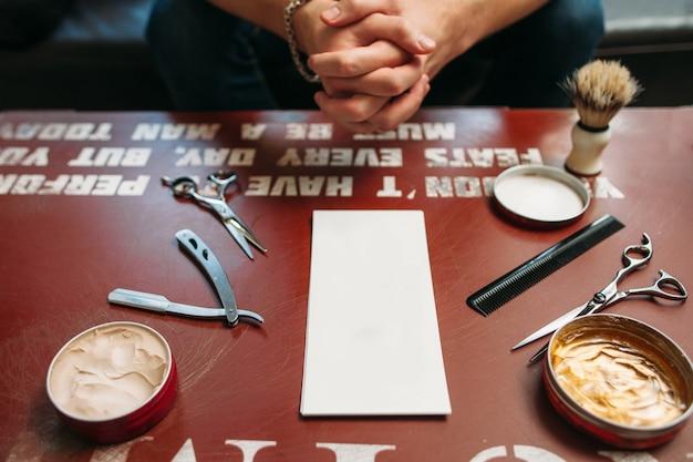 Scheda vuota con strumenti di barbiere sul tavolo