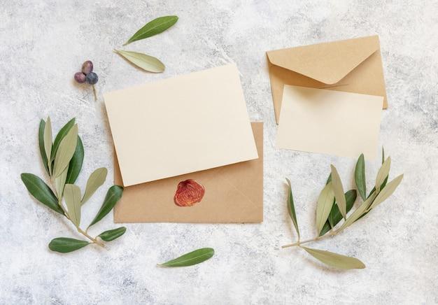 Carte bianche e buste sul tavolo con rami di ulivo