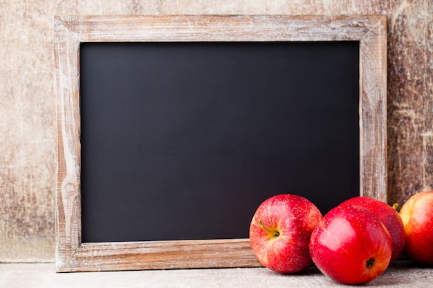 Lavagna in bianco con mele rosse sul tavolo in legno.