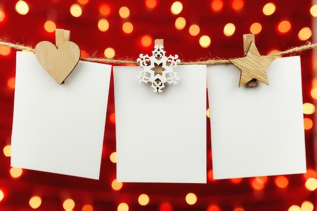 Cartoline d'auguri di natale in bianco che appendono sulla corda da bucato dell'annata