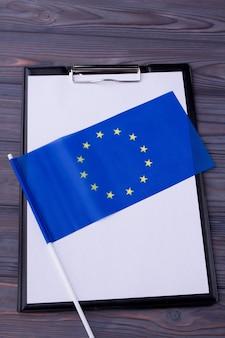 Appunti in bianco e bandiera blu dell'ue sulla scrivania in legno grigio