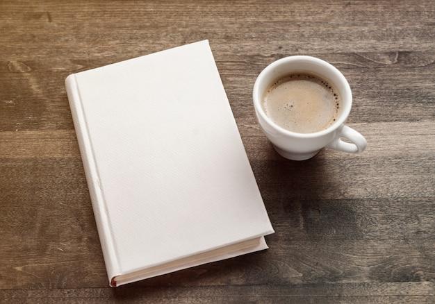 Libretto chiuso in bianco, matita e tazza di caffè su fondo di legno dell'annata. mockup di design reattivo.