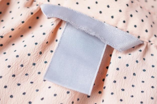 Etichetta di abbigliamento in bianco da vicino sulla trama del tessuto