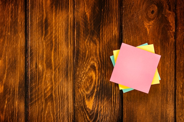 Adesivi colorati in bianco sulla tavola di legno marrone