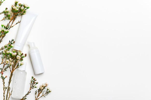 Mockup di flaconi per la cosmetica in bianco con sfondo vuoto di fiori. struccante