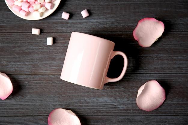 Tazza, petali e marshmallow vuoti sulla tavola di legno grigia