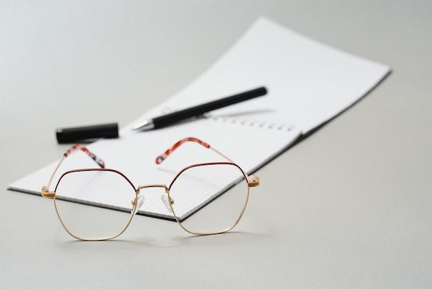 Diario vuoto, penna e occhiali su sfondo bianco