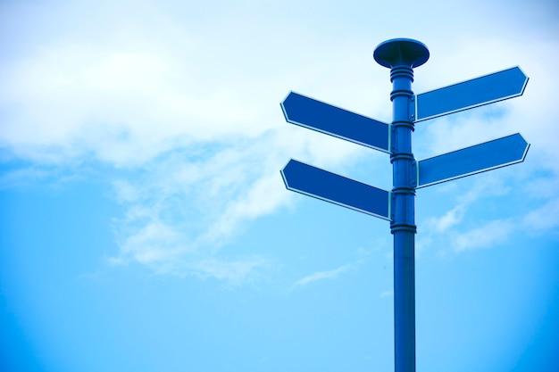 Segnale di direzione in bianco con 4 frecce sul fondo del cielo.
