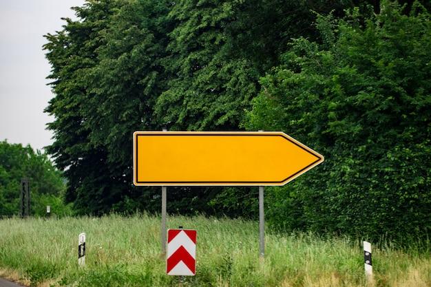 Segnali stradali direzionali in bianco contro il parco.