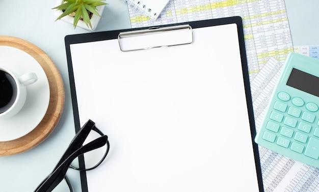 Documento vuoto sulla scrivania dell'ufficio, caffè, calcolatrice, occhiali e rendiconti finanziari.