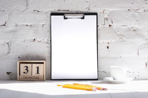 Immagine vuota vuota o foglio sul muro di mattoni bianchi con una tazza di caffè e matite. 31 dicembre, concetto di capodanno.