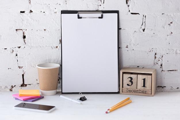Immagine vuota vuota o foglio sul muro di mattoni bianchi con smartphone e matite. copyspace, spazio negativo per la tua pubblicità. 31 dicembre, concetto di capodanno.