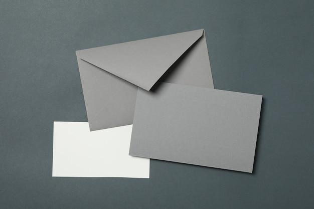 Busta e carte in bianco su fondo nero-chiaro, spazio per testo
