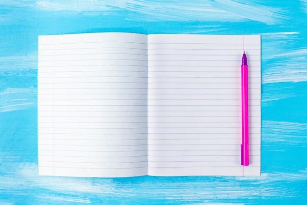 Foglio di quaderno vuoto e penna rosa.
