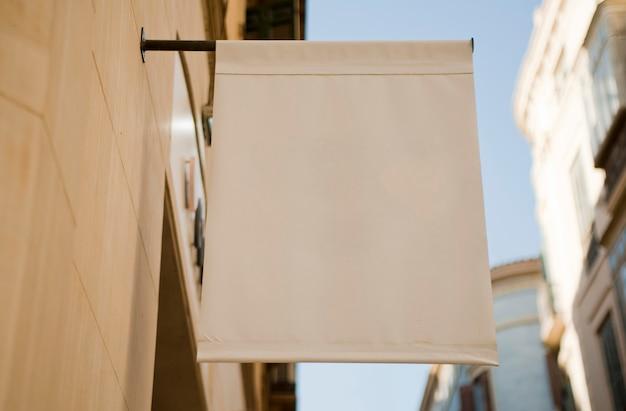 Bandiera in bianco o banner in tessuto appeso alla parete.