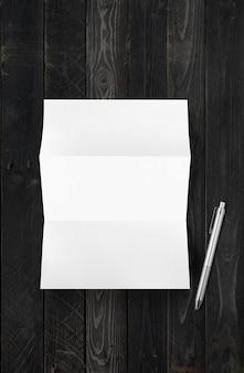 Mockup di foglio di carta a4 bianco piegato in bianco e penna isolato su fondo di legno nero