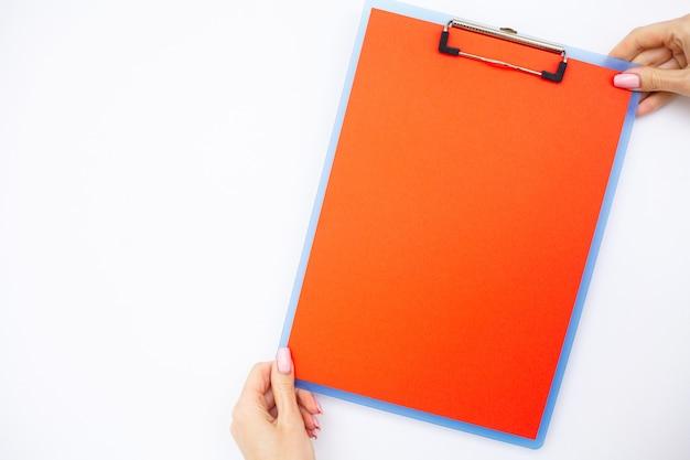 Cartella vuota con carta rossa. mano che tiene la cartella e la penna su sfondo bianco.