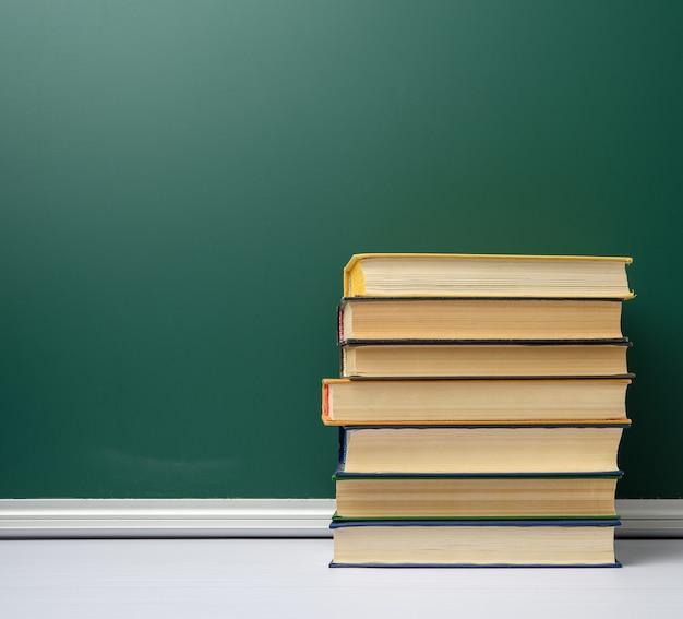 Bordo scolastico bianco gesso verde e pila di libri, torna a scuola, copia dello spazio