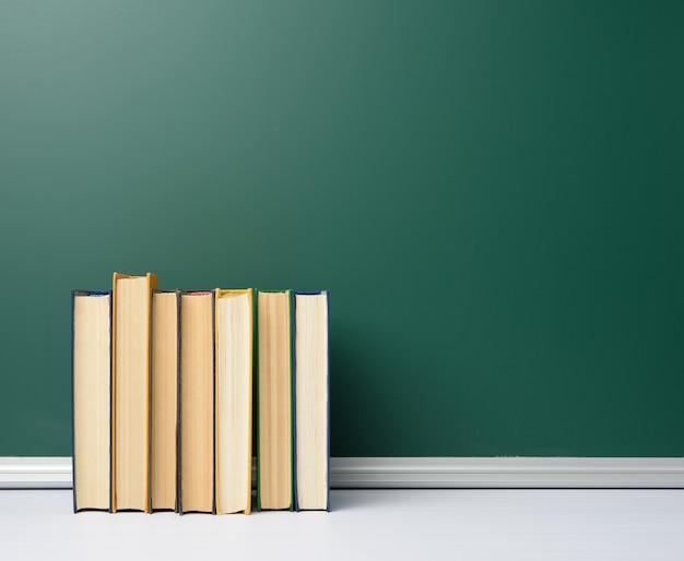 Consiglio scolastico in bianco del gesso verde e pila di libri, torna a scuola