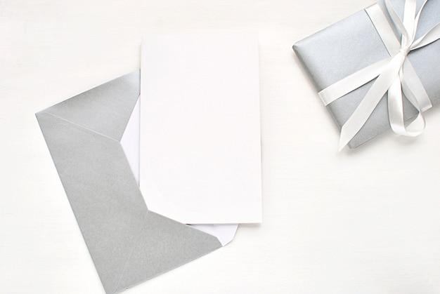 Cartolina d'auguri in bianco, invito con busta d'argento e regalo per natale.