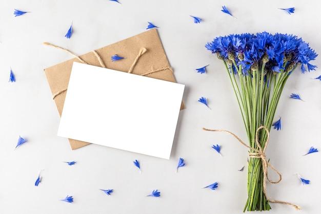 Biglietto di auguri vuoto con bouquet di fiordalisi blu estivo su superficie di marmo bianco