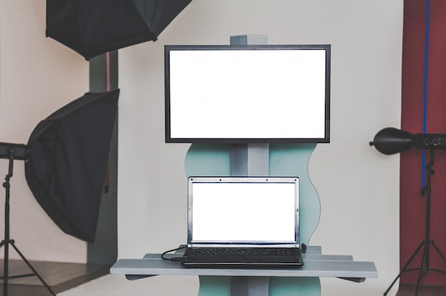 Computer portatile e monitor in bianco nello studio fotografico con le sorgenti luminose.