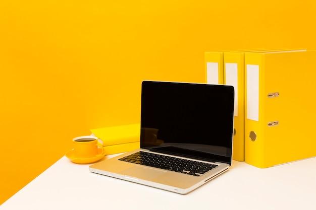 Laptop vuoto e cartelle gialle