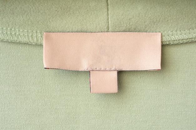 Etichetta vuota dei vestiti per la cura del bucato sul fondo di struttura del tessuto verde