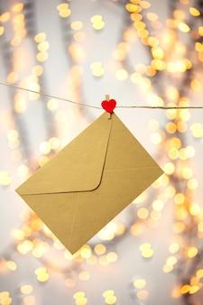 Lettera vuota, busta o biglietto di auguri appeso con cuori rossi, romantica lettera d'amore, sfondo bokeh di concetto di san valentino, design romantico spazio copia