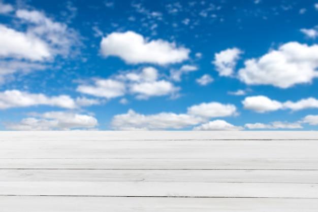 Tavolo in legno grigio chiaro vuoto su uno sfondo di cielo nuvoloso blu sfocato per la dimostrazione e il montaggio di prodotti e cose.
