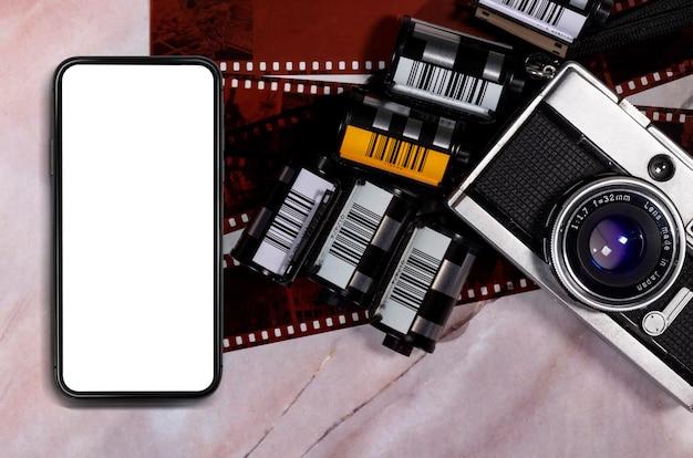 Vuoto del telefono cellulare sul tavolo in marmo e fotocamera vintage
