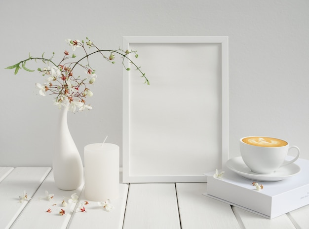 Cornice vuota mockup, tazza di caffè, candela e bellissimi fiori di clerodendron annuendo in vaso di ceramica moderno sulla superficie di legno bianco tavolo in legno, colazione nell'interno della stanza bianca