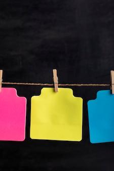 Le carte di carta eterogenee vuote appendono con la molletta sulla corda. cornice verticale. copia spazio. posto per il tuo testo.