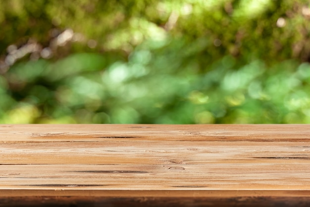 Tavolo in legno naturale vuoto su uno sfondo sfocato di foglie verdi con bokeh per la dimostrazione e il montaggio di prodotti e cose.