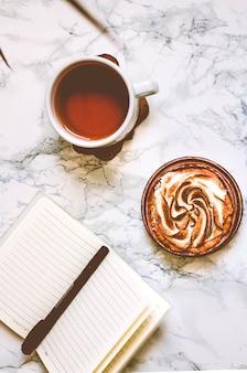 Taccuino in bianco una tazza di tè e torta vista dall'alto con spazio di copia luogo di lavoro concetto di piallatura tono