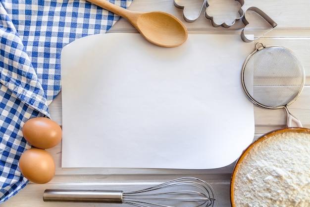 Nota vuota per ricetta con utensili da cucina intorno, vista dall'alto