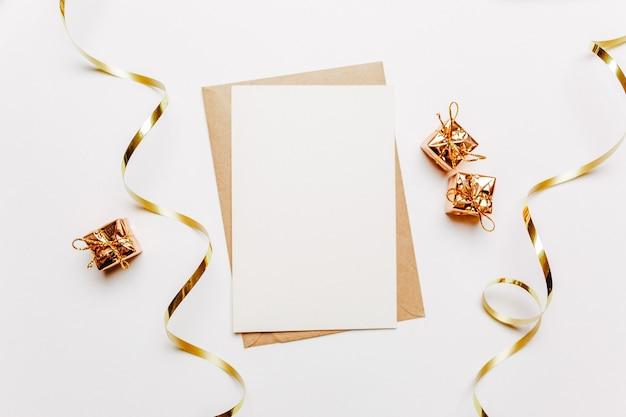 Nota vuota con busta, regali e nastro d'oro su bianco