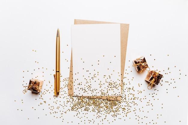 Nota vuota con busta, regali, penna e stelle glitter oro su sfondo bianco