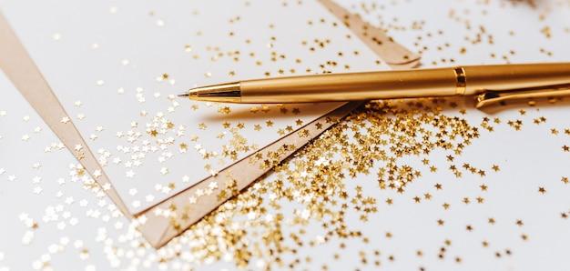 Nota vuota con busta, penna e stelle glitter oro su sfondo bianco